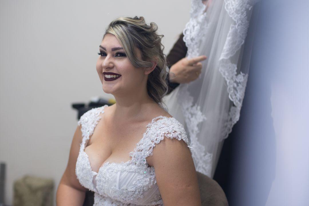fotografia da noiva sorrindo se olhando no espelho