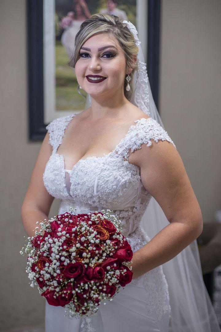 fotografia da noiva segurando o buque vermelho e sorrindo