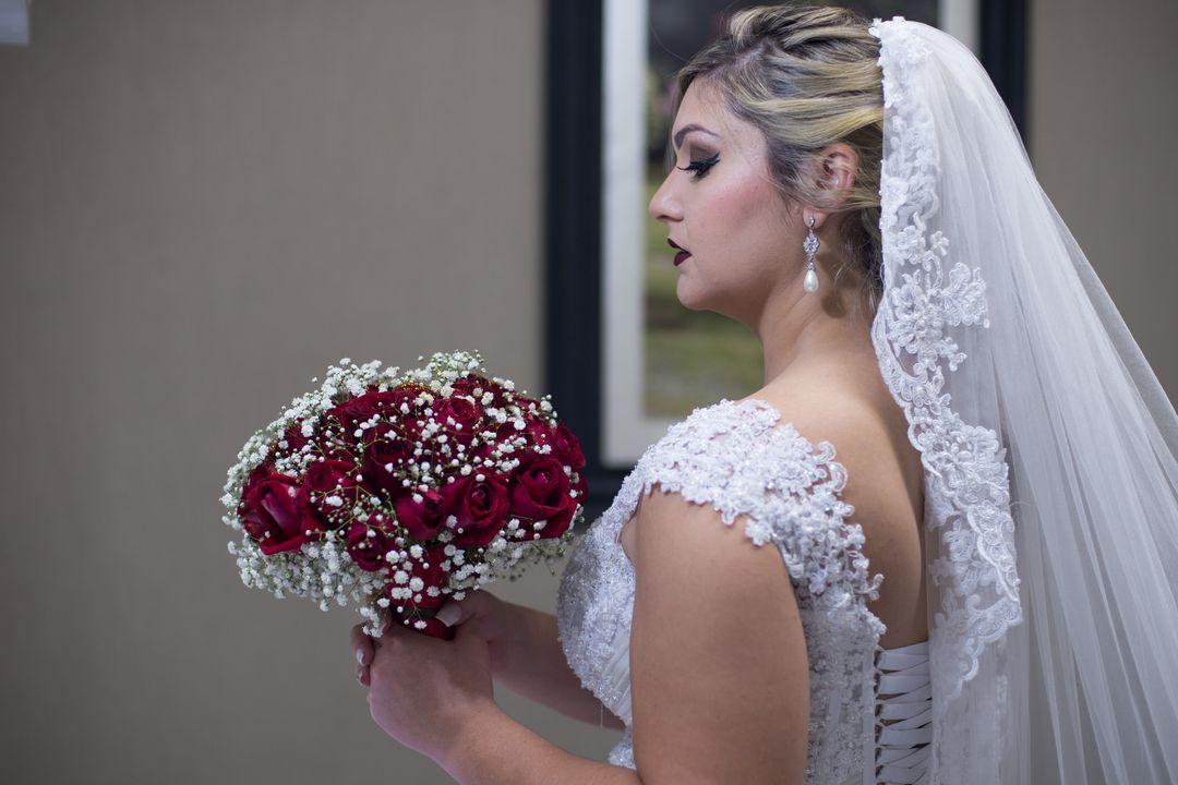 fotografia da noiva de lado olhando para seu buque vermelho