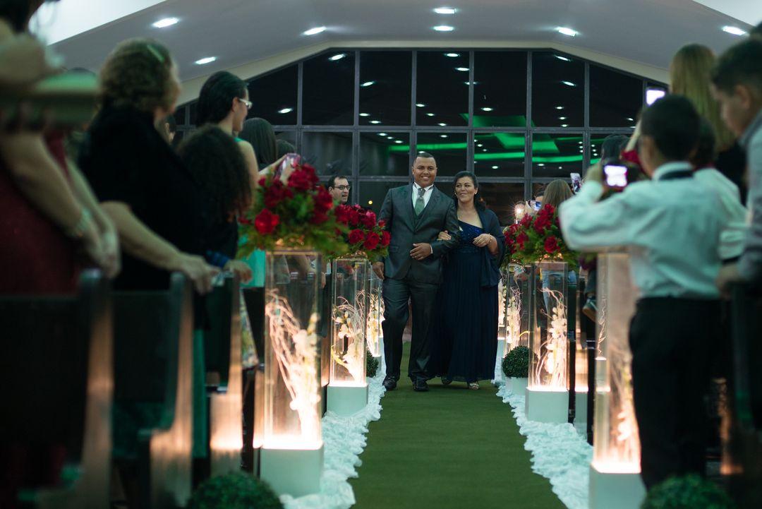 fotografia do noivo com sua mãe andando pelo corredor rumo ao altar
