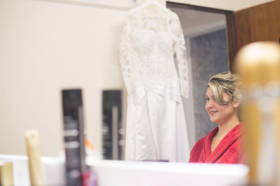fotografia da noiva no salão se arrumando ao lado do seu vestido de noiva