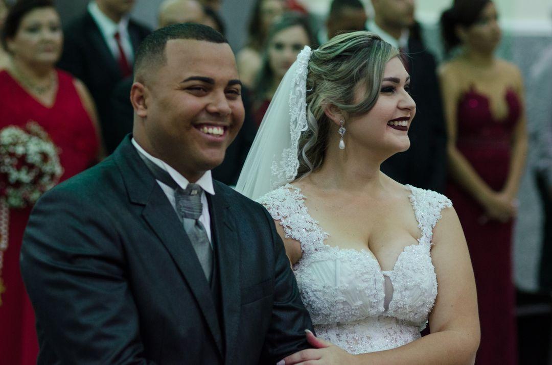 fotografia dos noivos sorrindo no altar