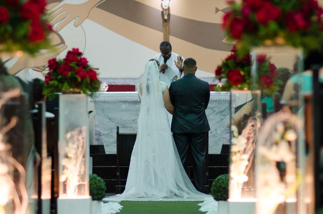 fotografia dos noivos em cima do altar de frente para o padre