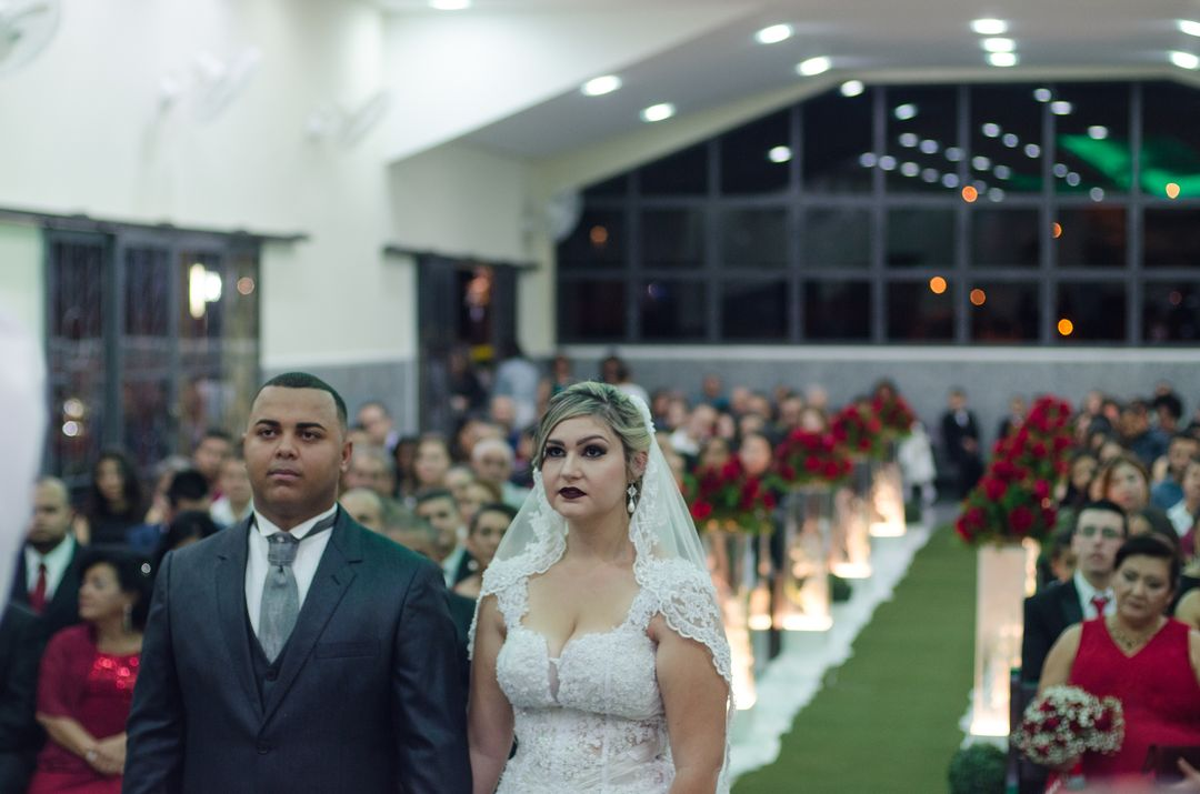 fotografia dos noivos no altar com convidados no fundo