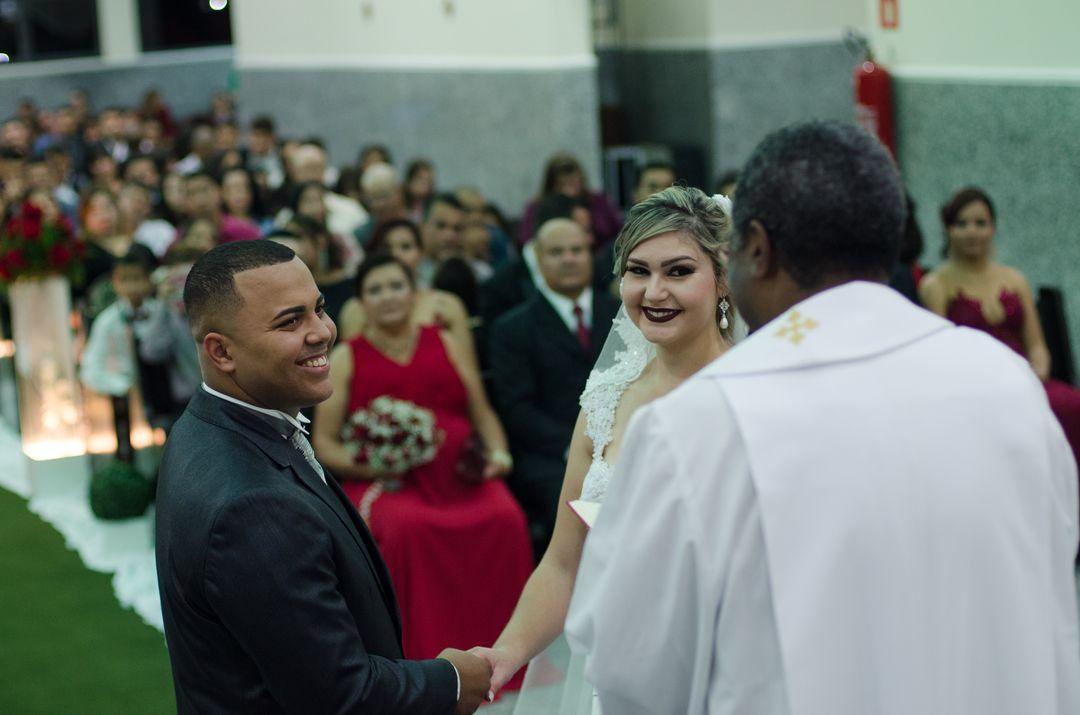 fotografia dos noivos olhando para o padre