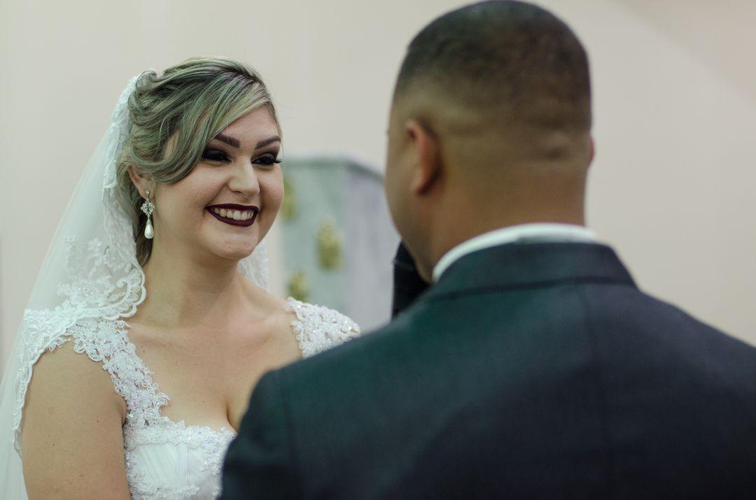fotografia da noiva sorrindo ao escutar o noivo falando os votos