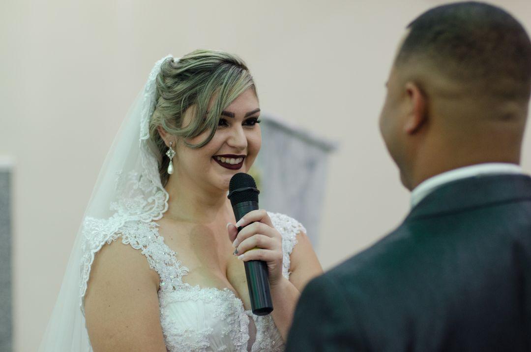 fotografia da noiva falando ao microfone os votos para o noivo