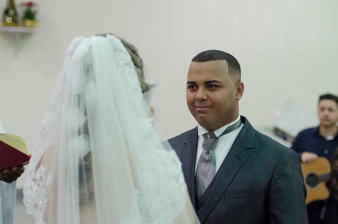 fotografia do noivo sorrindo para a noiva escutado os votos dela