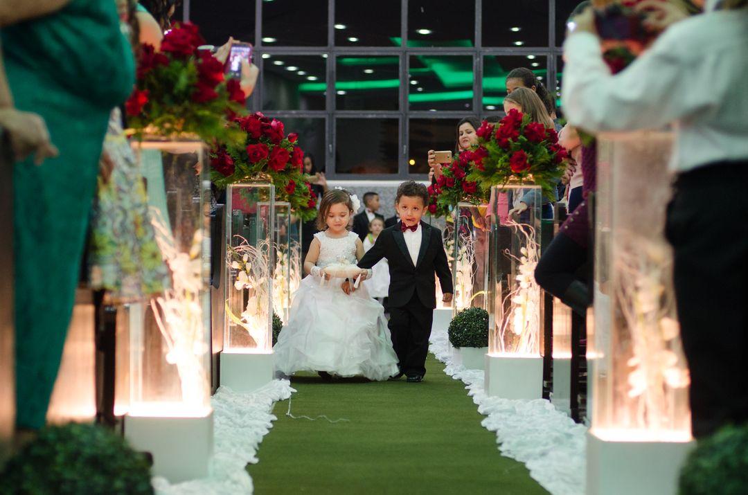 fotografia dos porta alianças entrando no corredor rumo ao altar