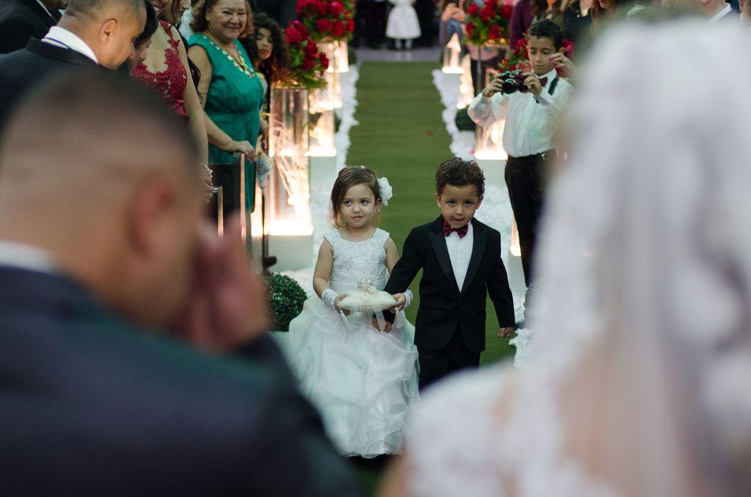 fotografia dos porta alianças rumo ao altar com a moldura do noivo e noiva