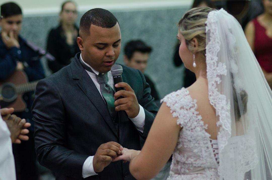 fotografia do noivo falando ao microfone e colocando aliança na noiva