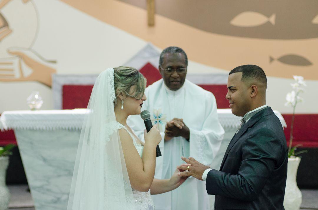 fotografia da noiva falando ao microfone e colocando a aliança na mão do noivo
