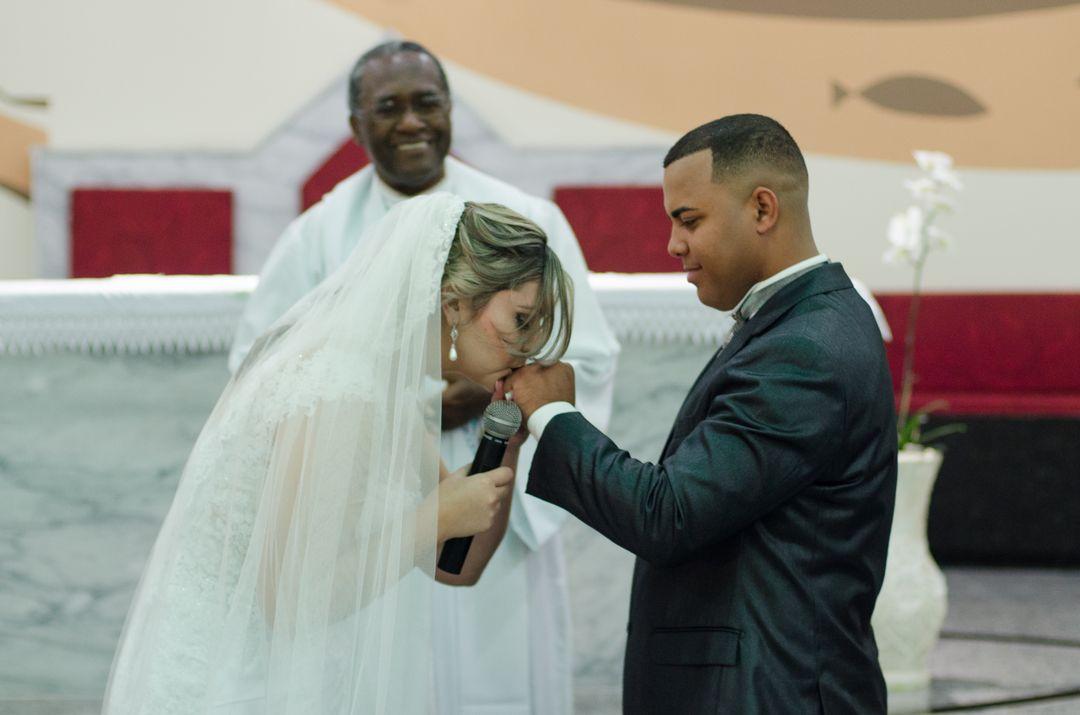 fotografia da noiva beijando a mão do noivo apos ter colocado a aliança