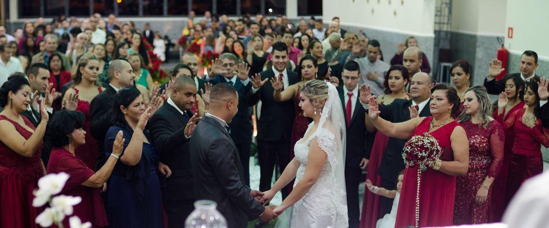 fotografia de todos os padrinhos estendendo as mãos para o casal em oração