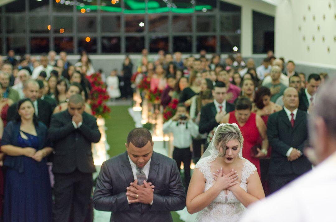 fotografia do casal de joelhos rezando em cima do altar
