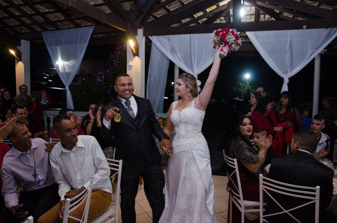 fotografia do casal chegando na festa e noiva levantando o buque