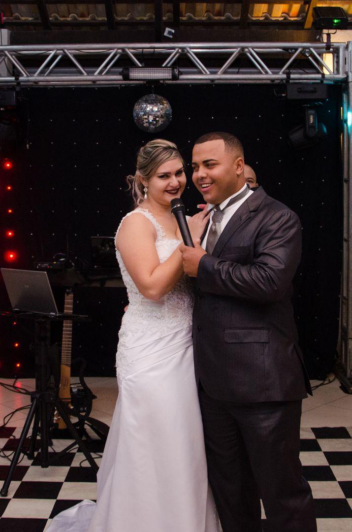 fotografia dos noivos abraçados falando o microfone para os convidados