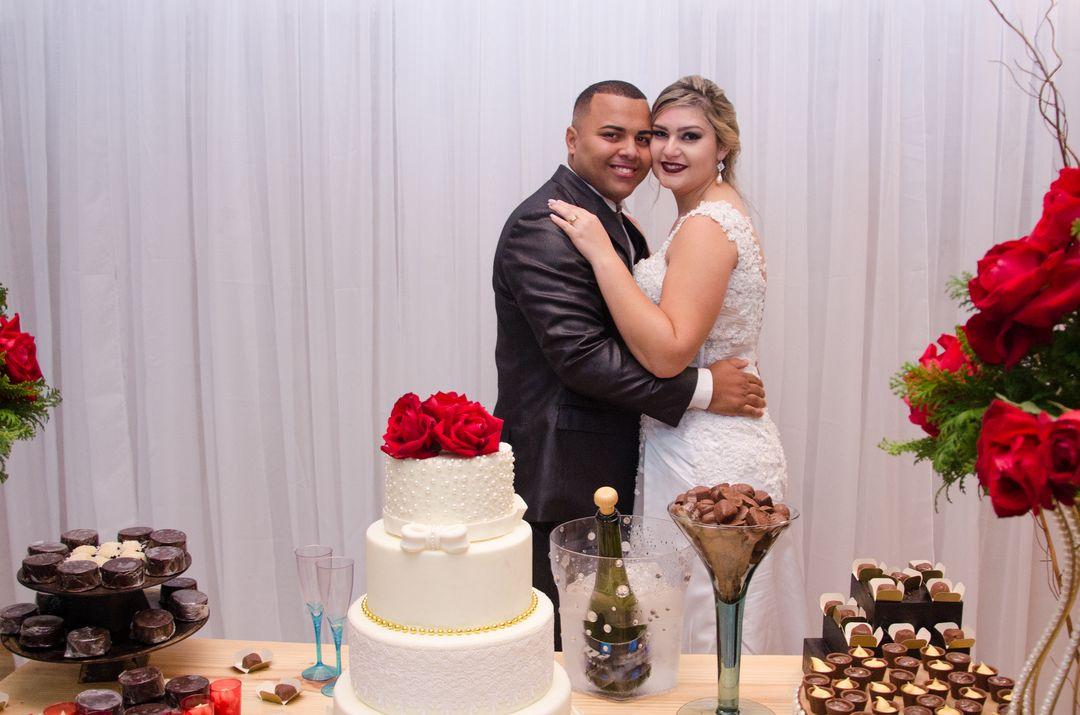 fotografia dos noivos abraçados na mesa do bolo