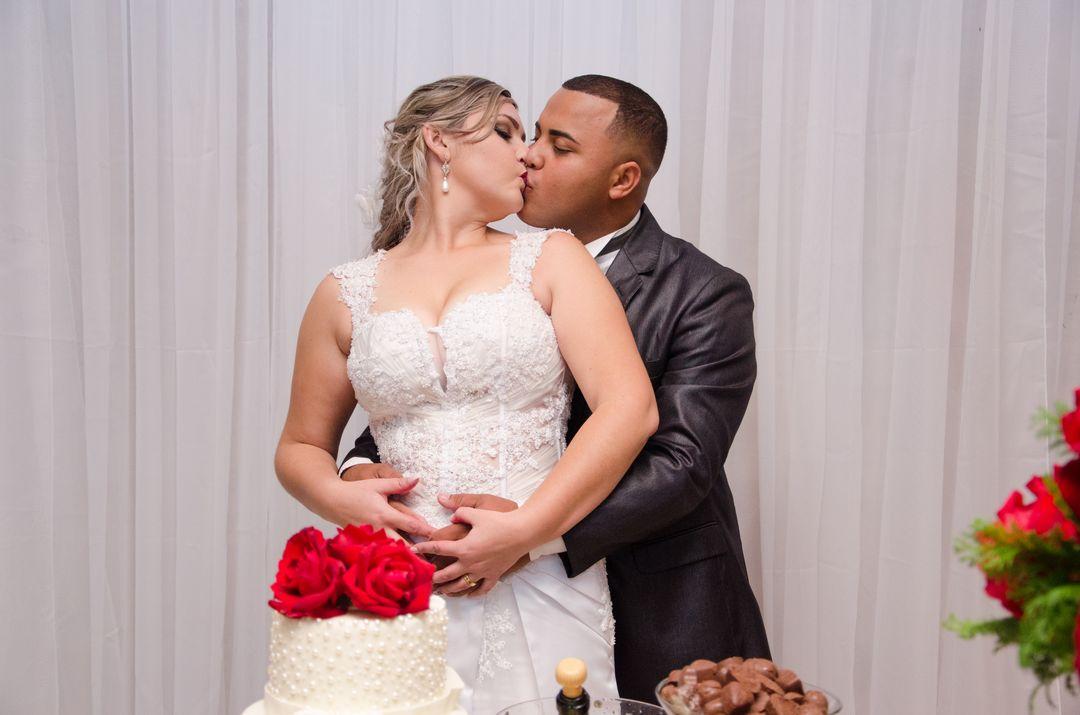 fotografia do casal de beijando na mesa do bolo