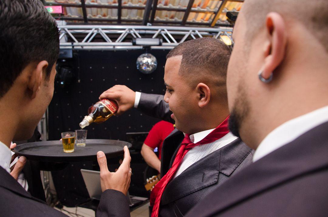 fotografia do noivo colocando wisk em copo