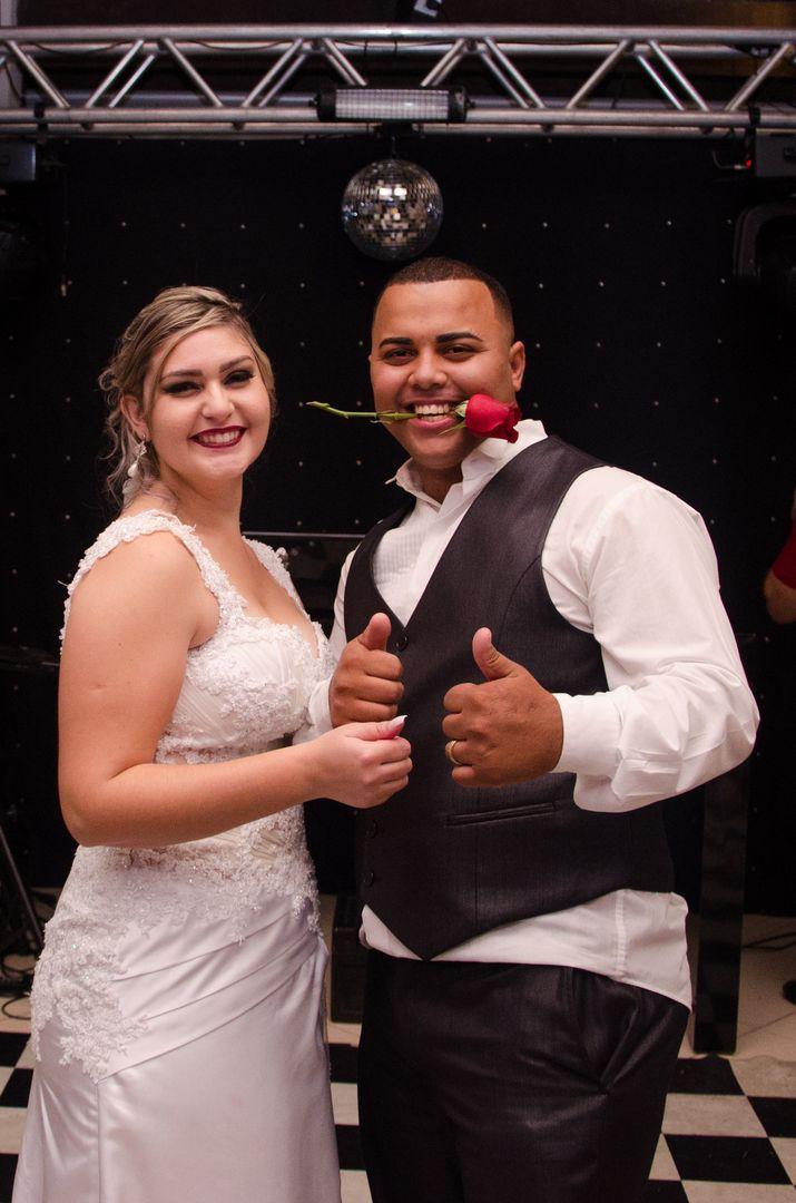 fotografia do casal e o noivo com uma rosa da boca
