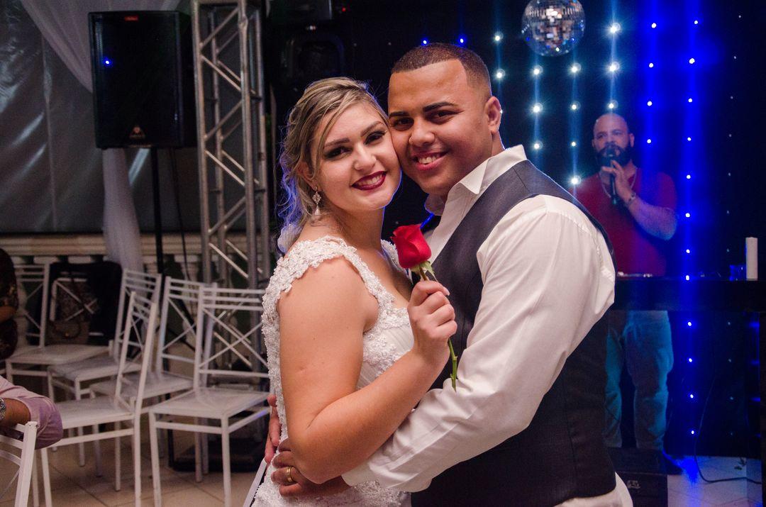fotografia do casal e noiva segurando uma rosa na mão