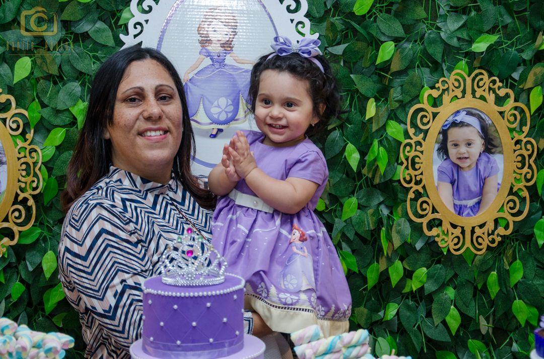 fotografia da sophia na mesa do bolo com sua avó sorrindo