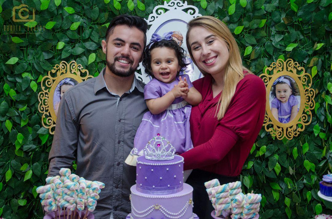 fotografia da sophia com convidados na mesa do bolo