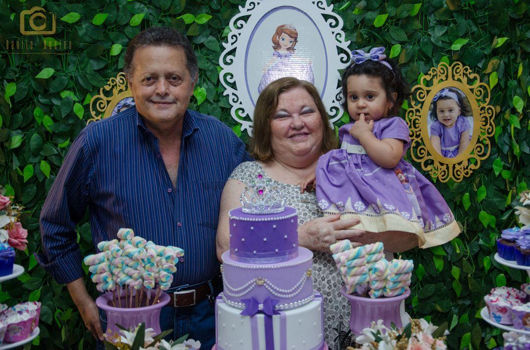 fotografia de familiares segurando sofia no colo na mesa do bolo