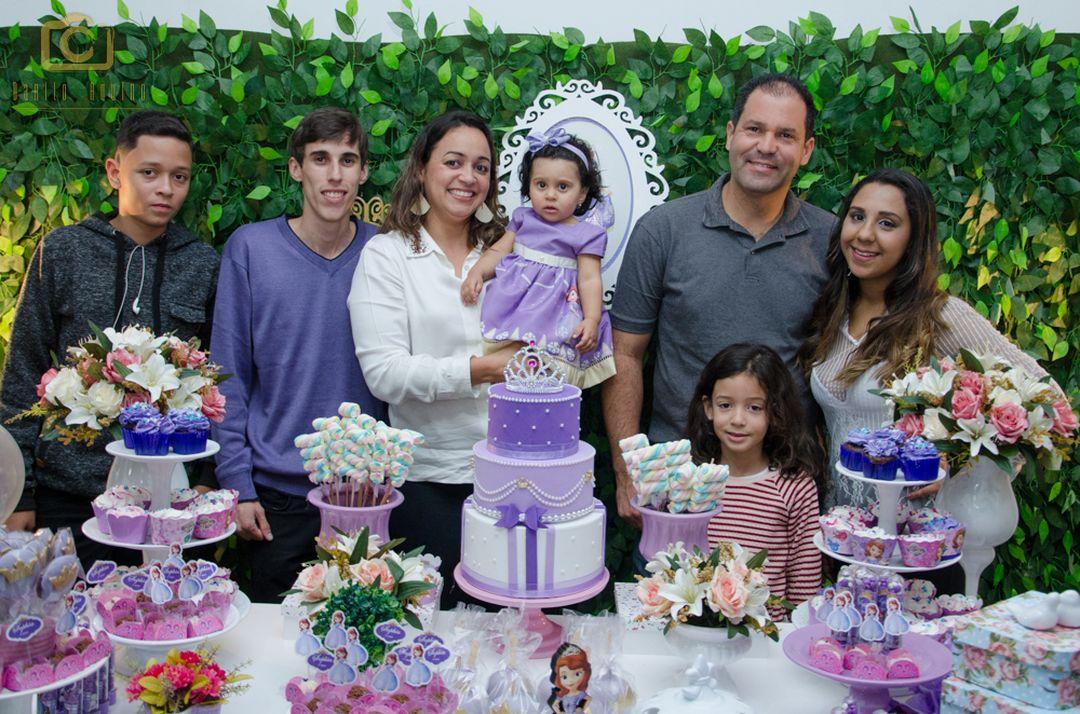 fotografia de sophia com familiares na mesa do bolo