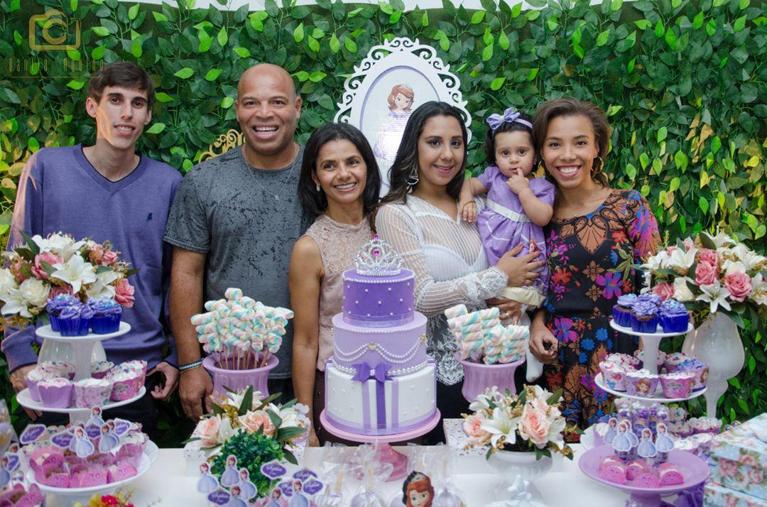 fotografia da sophia com familiares na mesa do bolo