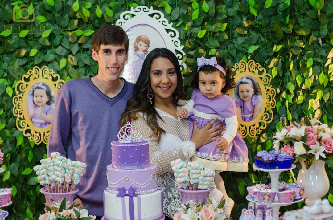 fotografia da sophia com seus pais fernando e lizandra na mesa do bolo
