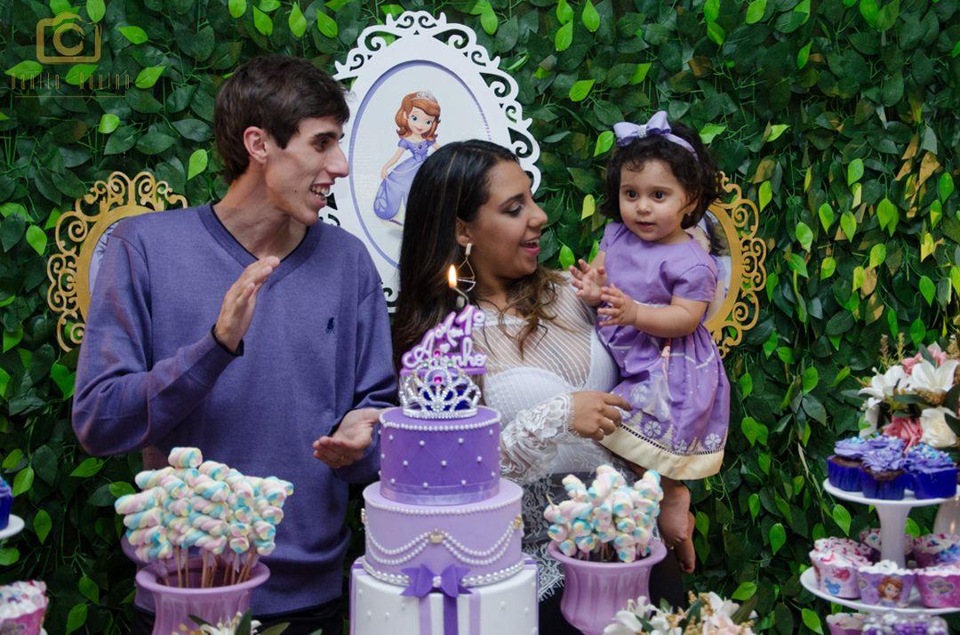 fotografia da mãe lizandra segurando a sophia com o pai fernando ao lado cantando parabéns