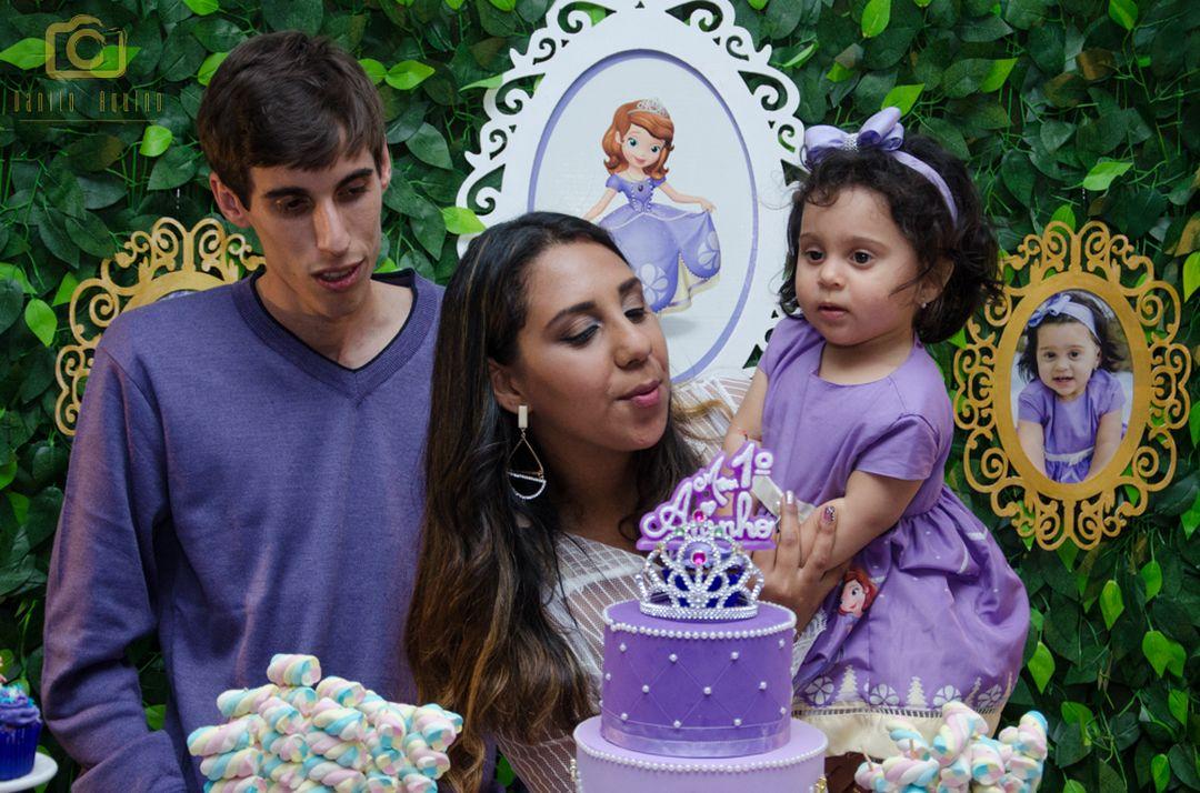fotografia da mãe lizandra soprando a vela para sophia e pai fernando ao lado