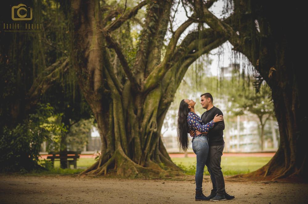 fotografia do casal em pé no meio das arvores