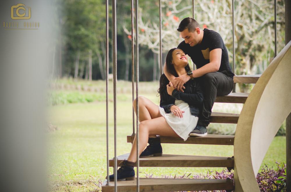 fotografia do casal sentados na escada sorrindo um para o outro