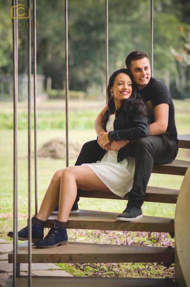 fotografia do casal sentados na escada olhando para o horizonte