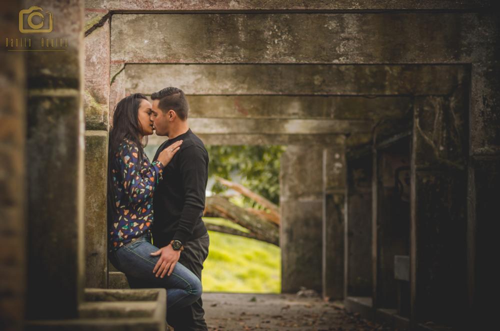 fotografia do casal se beijando contra a parece em pé