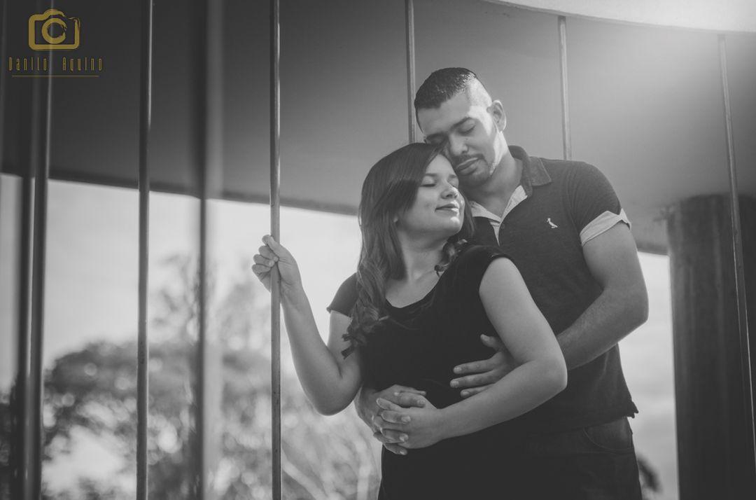 fotografia preta e branca do casal em escada e com luz do sol entrando ao lado direito
