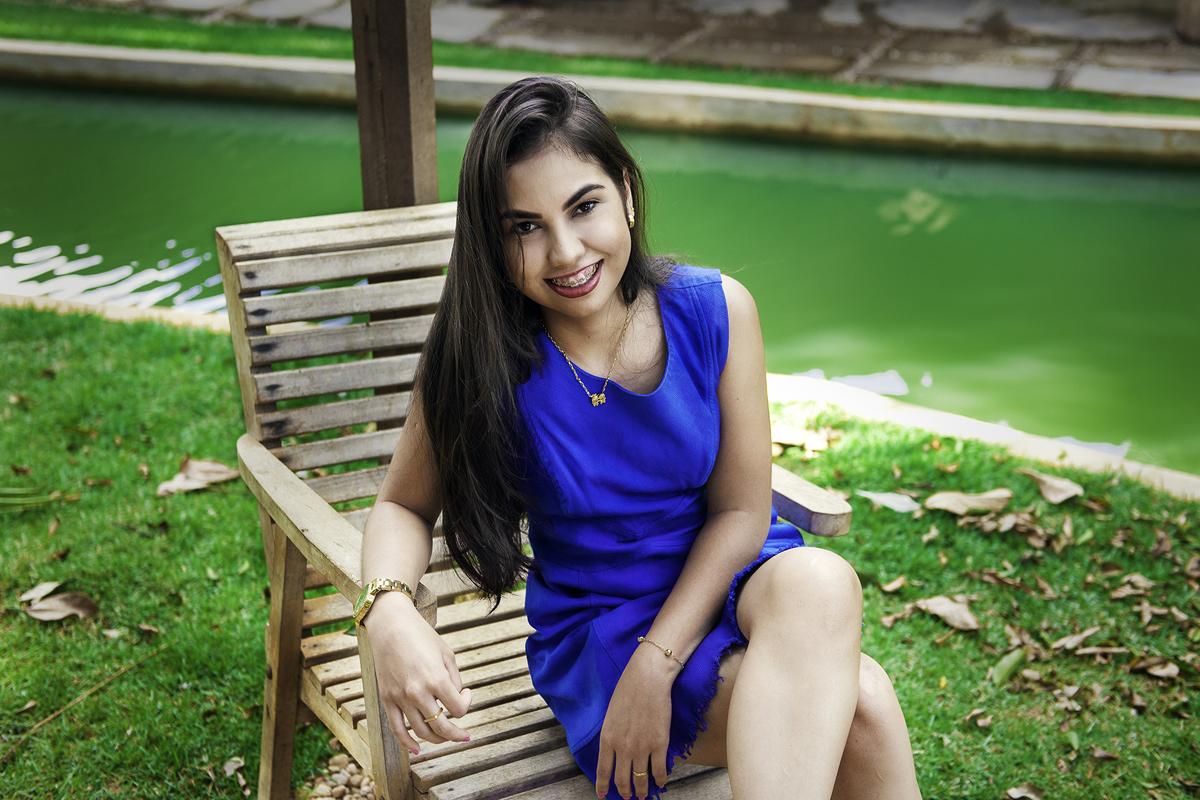 fotos externas ao ar livre no pesque e pague juliana roves por gabriel silvério em vilhena rondonia com vestido azul em cadeira de madeira