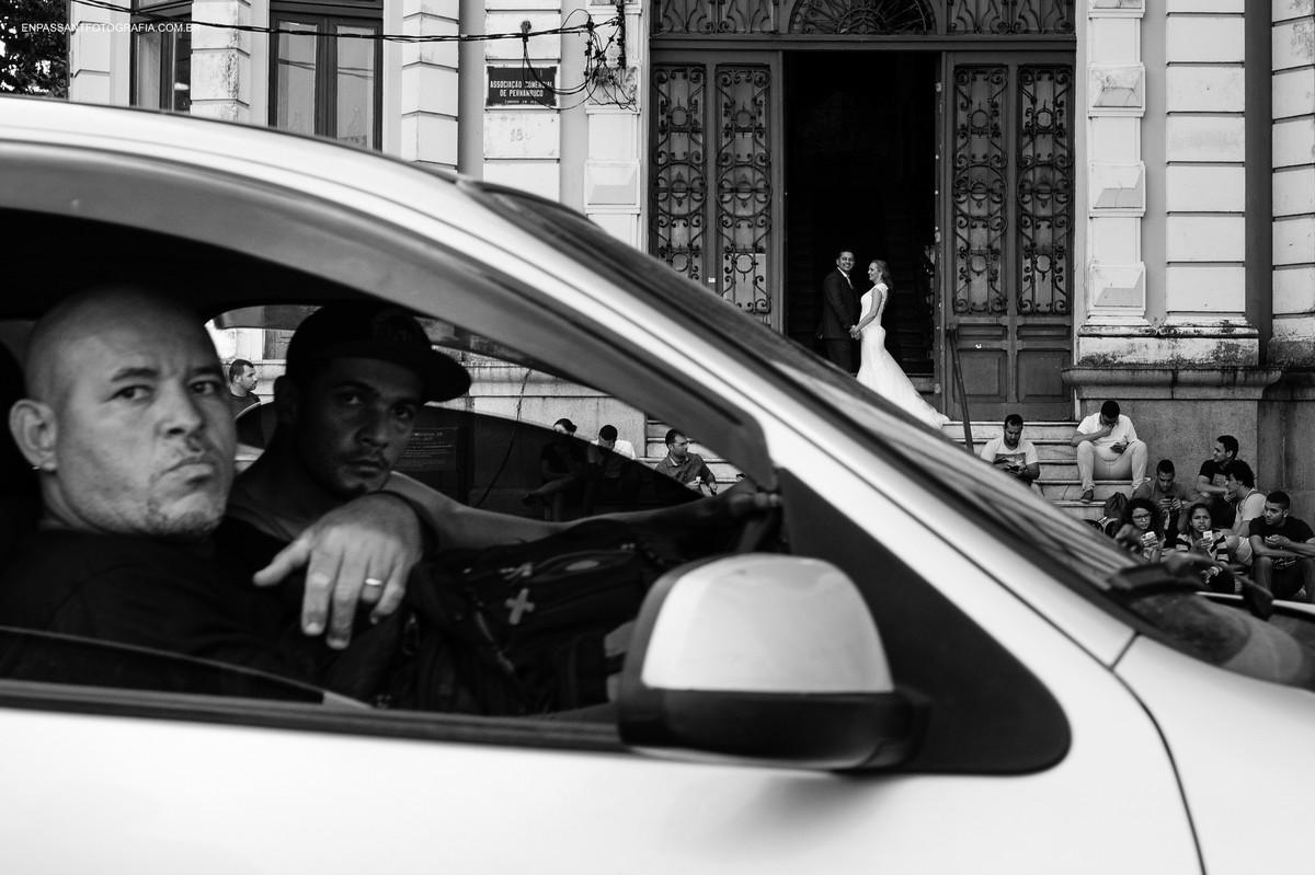 noivos abraçados enquanto carro passa