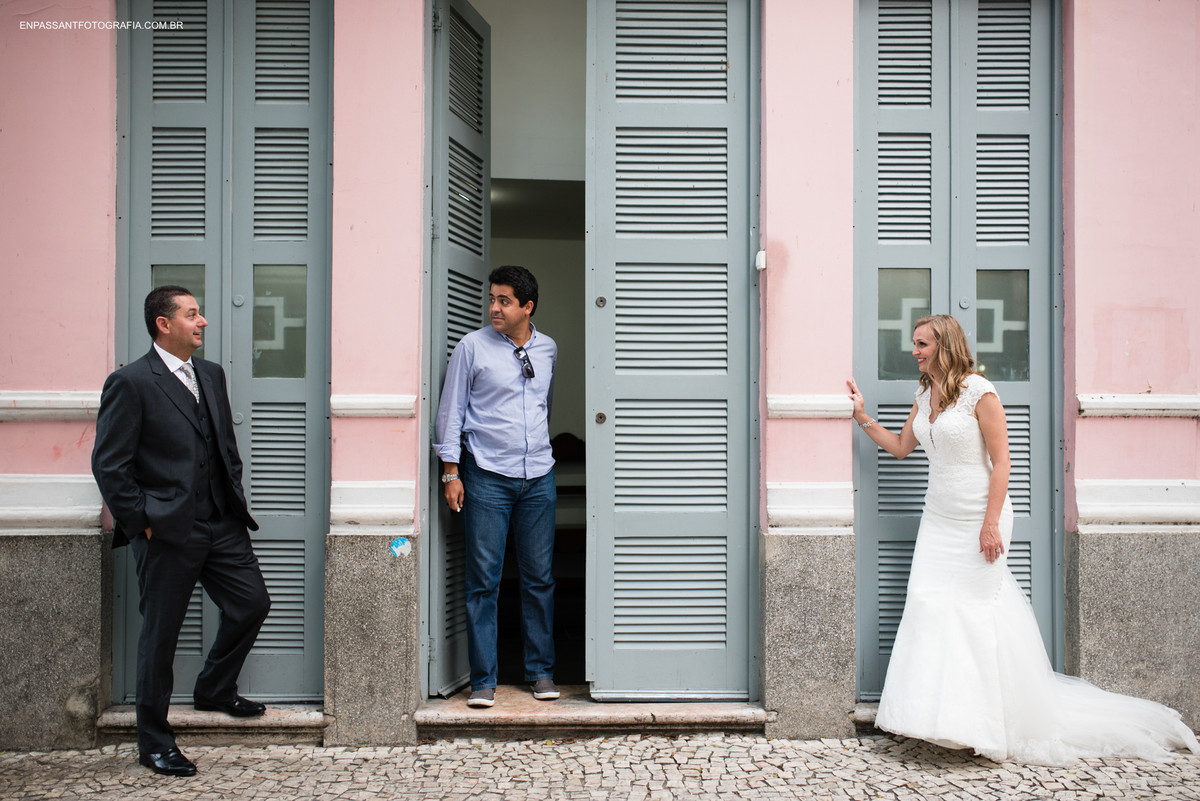 homem sai pela porta enquanto noivos se olham