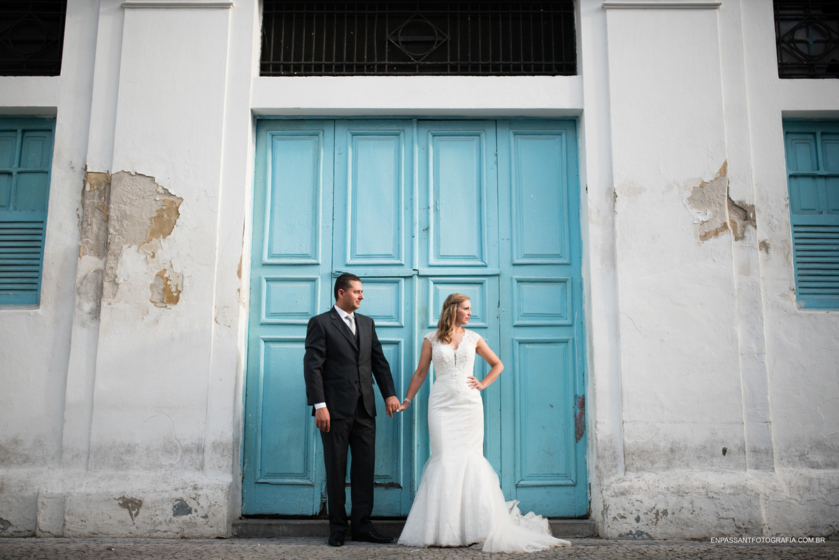 noivos em pé de mãos dadas na frente de uma porta azul