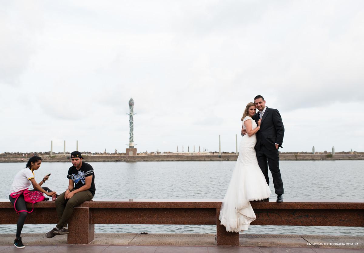 noivos em cima de um banco com pessoas olhando