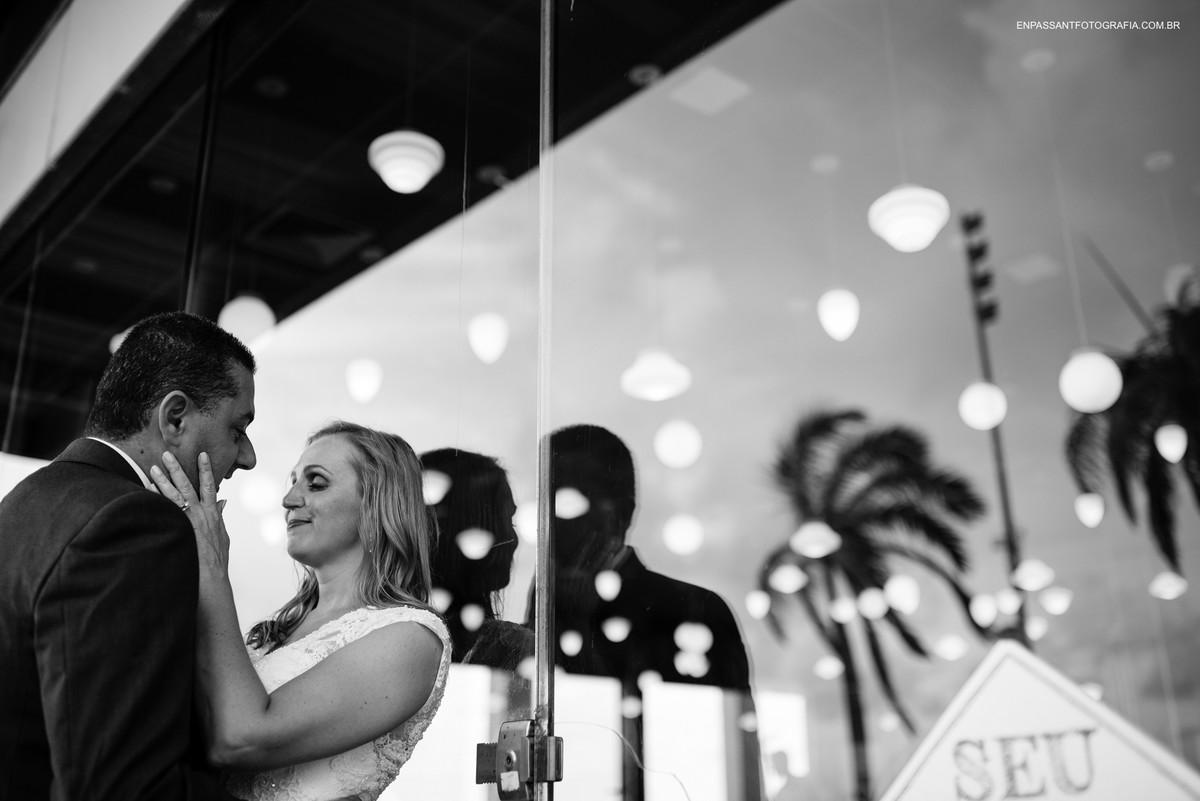 noivos abraçados encostados num vidro