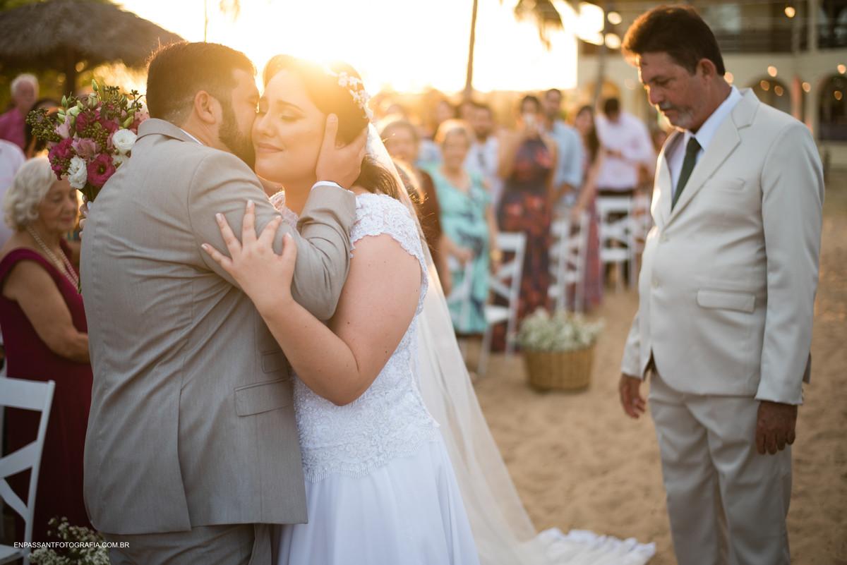 noivos se abraçam enquanto pai olha
