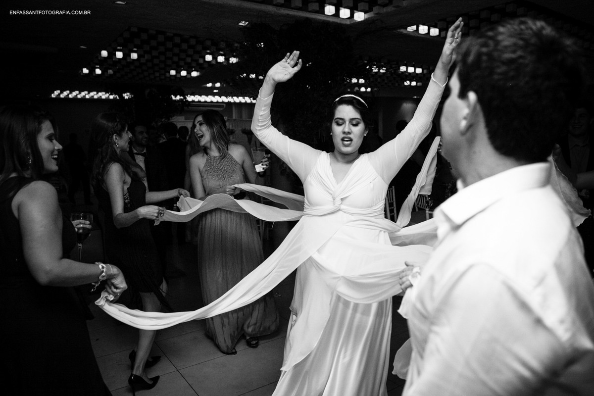 mulheres pegam partes do vestido da noiva com braços levantados
