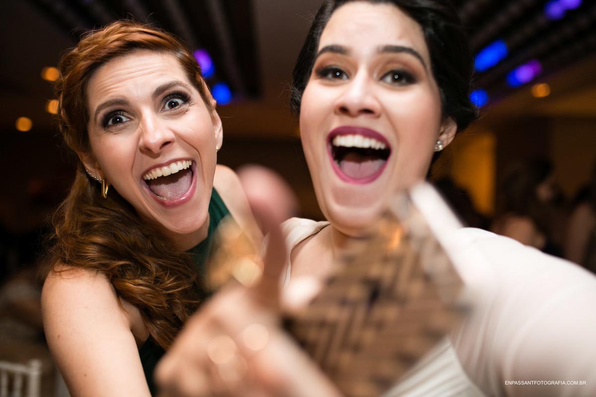 noiva e madrinha apontam para a câmera