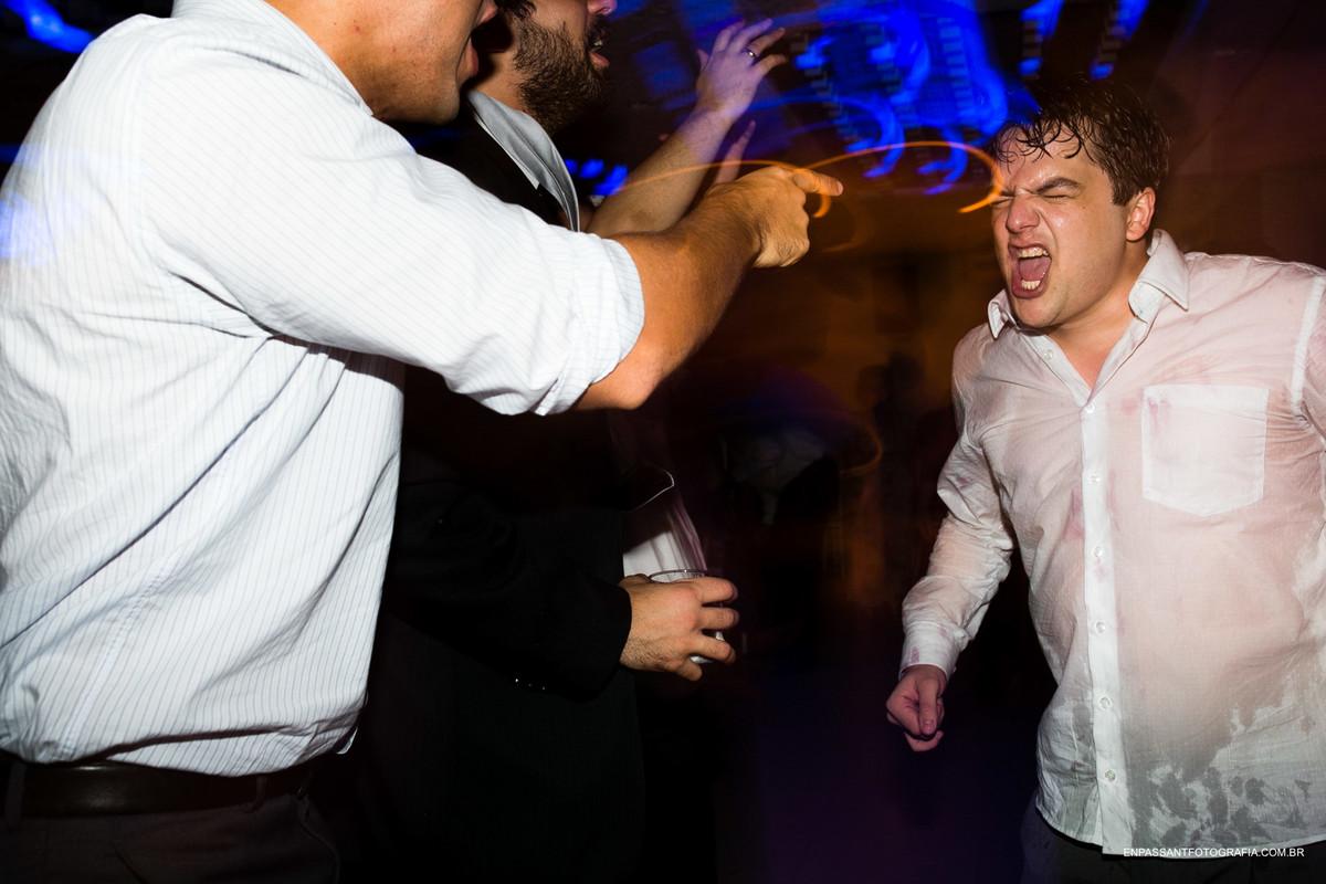 noivo dançando e amigos apontando para ele