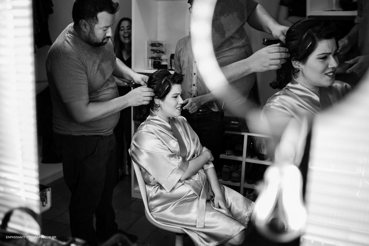 maquiador arrumando o cabelo da noiva sentada com reflexo no espelho